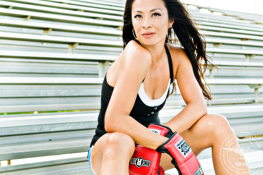 natural light lifestyle fitness portrait of girl in boxing gloves taken on football stadium bleachers in plano texas