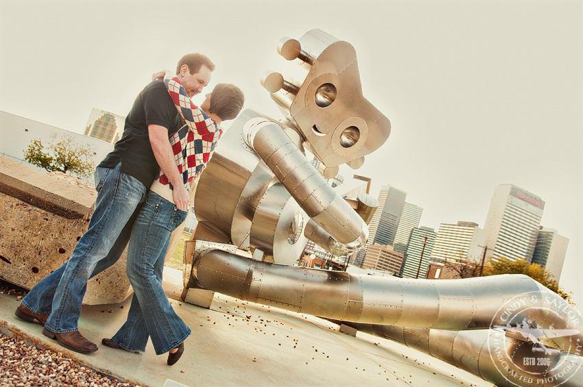 an engagement portrait in downtown dallas deep elum area in front of metal robot sculpture by artists Brad Oldham and Brandon Oldenburg