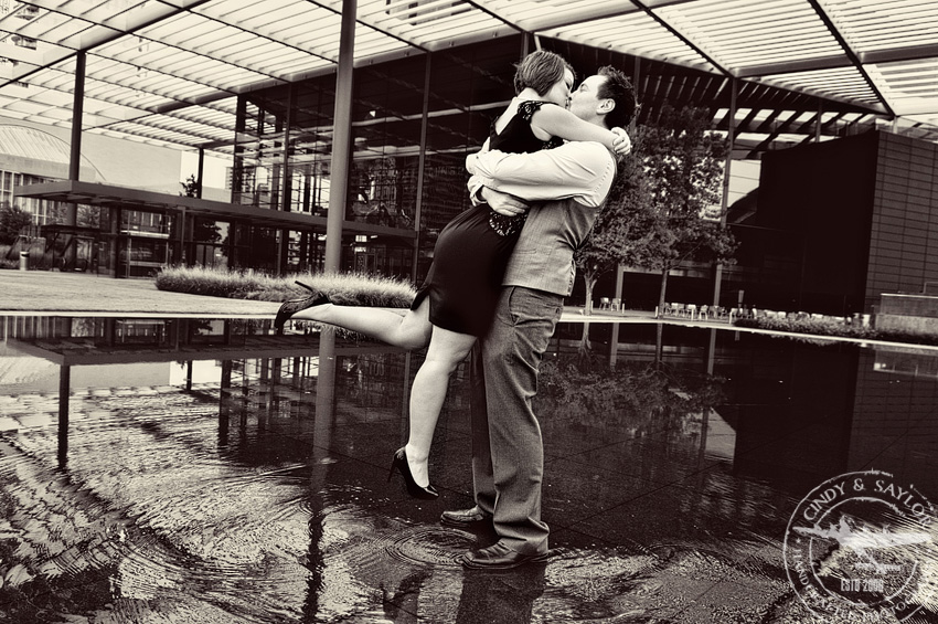 engaged couple in reflecting pool in front of the winspear opera house dallas texas