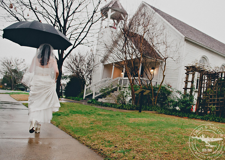 bride going to ceremony in the rain in front of a historic chapel in mckinney texas