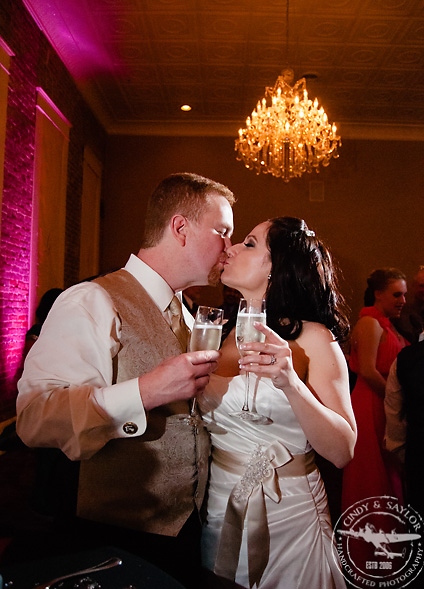 bride and groom toasting at rick's chophouse ballroom at the grand hotel in mckinney texas
