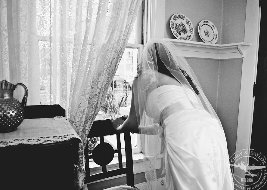 bride peeking at guests arriving in vintage farmhouse in mckinney