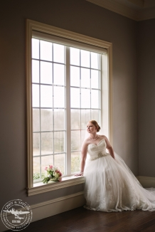 bride in front of large window Bridal session at The Milestone in Denton Texas